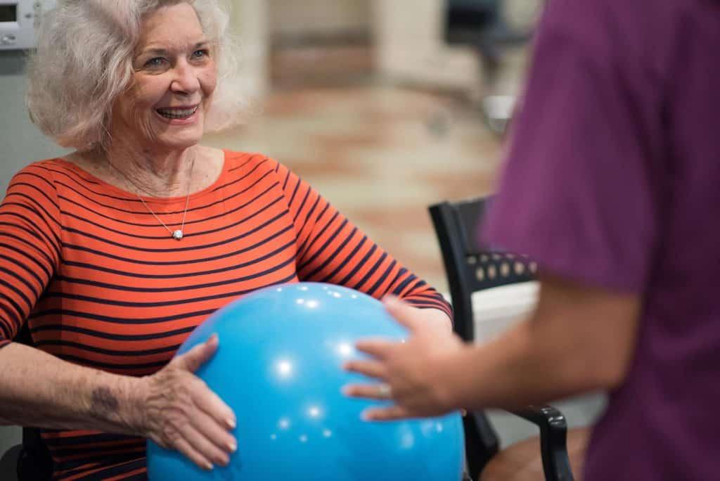 Senior woman holding rubber ball with nurse