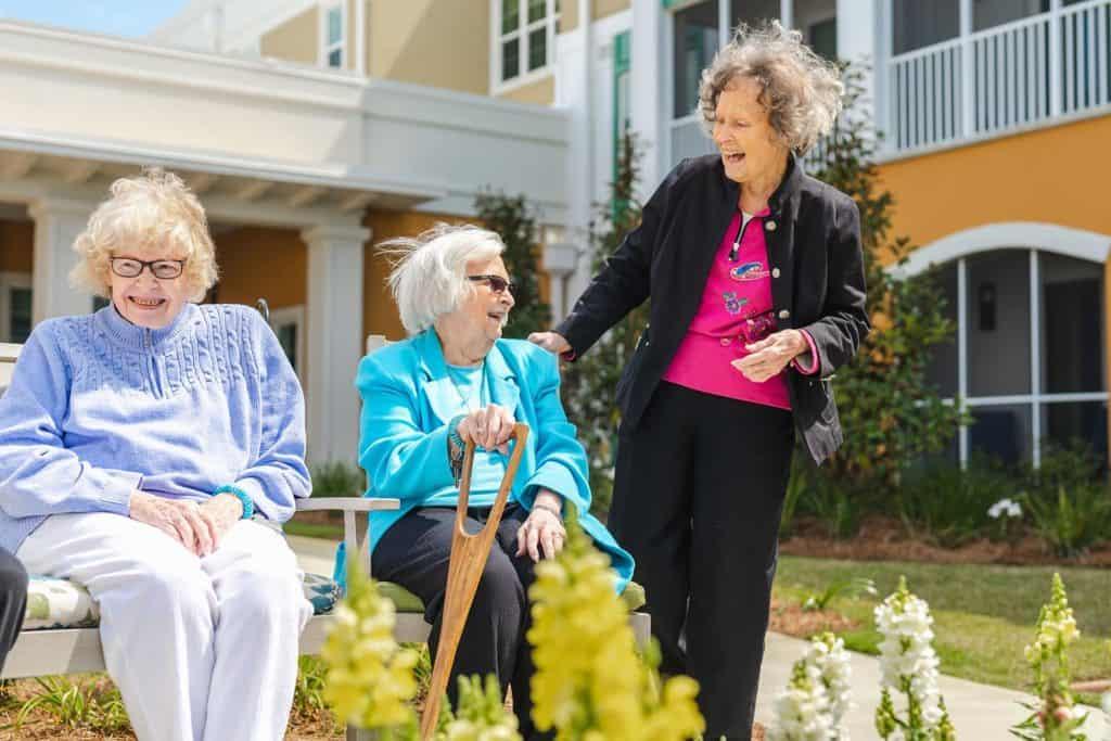 Three senior women socializing in courtyard