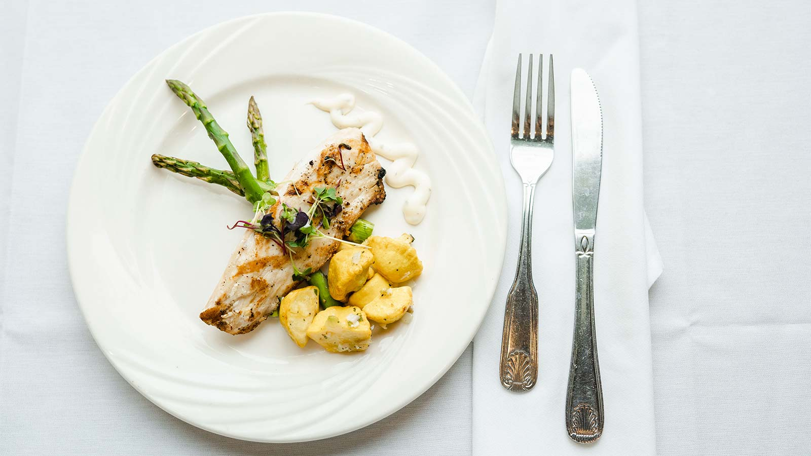 View of elegantly plated grilled chicken breast with potatoes and asparagus