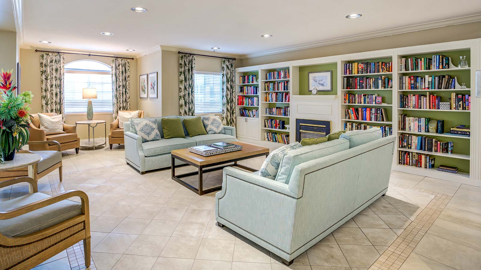 View of library with comfortable couches and chairs with fireplace at Heron Club at Prestancia an assisted living and memory care community in Sarasota FL