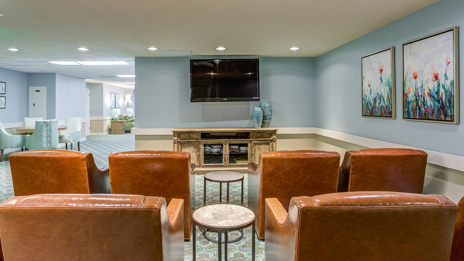 View of movie theatre area with comfortable chairs with fireplace at Heron Club at Prestancia an assisted living and memory care community in Sarasota FL