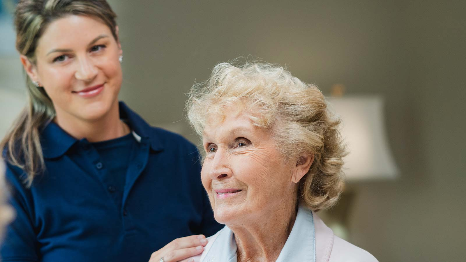 Senior woman seated with staff member standing by their side with hand on shoulder