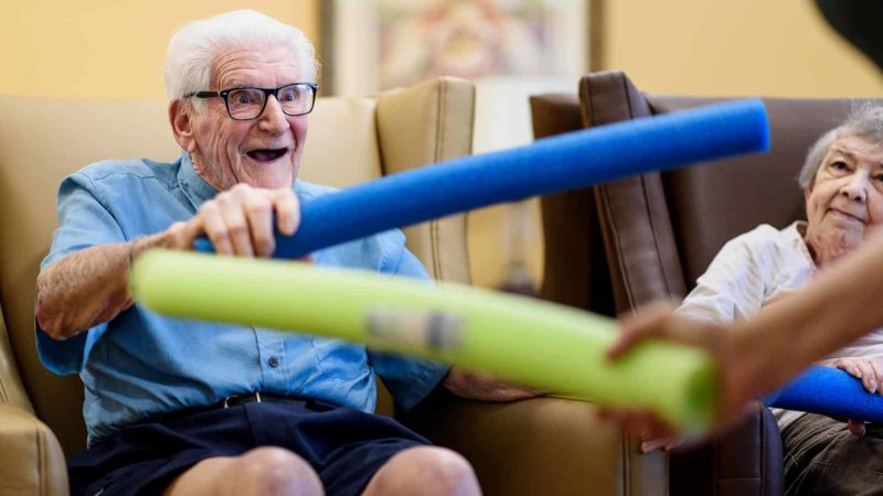 Senior man holding foam pool noodle during an activity