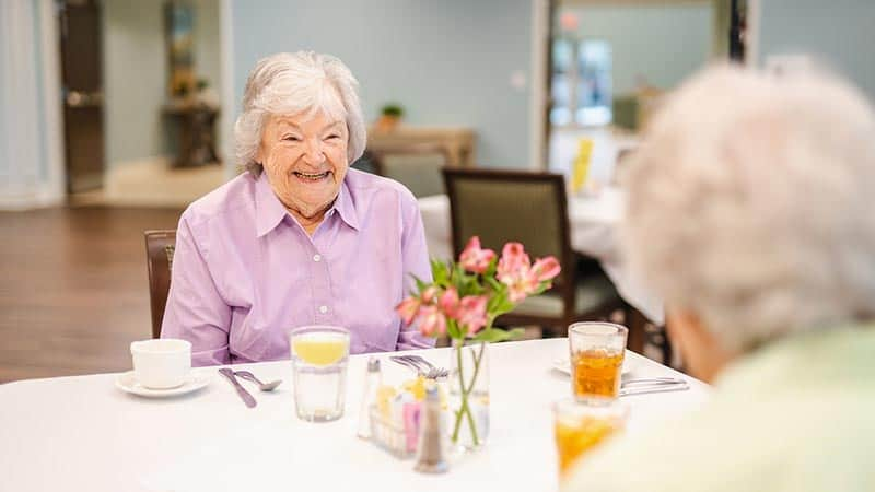 Smiling senior woman seated across from another woman