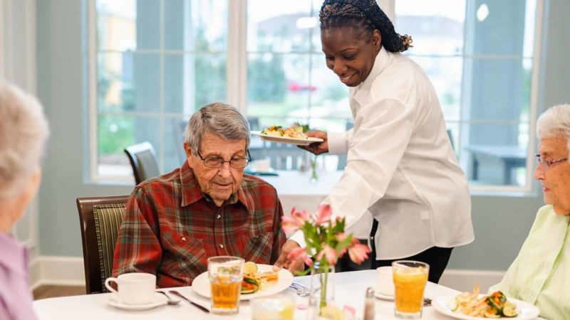 Dining staff serving meal to senior man seated at dining room table