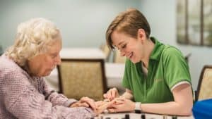 Staff member helping senior woman with nail care