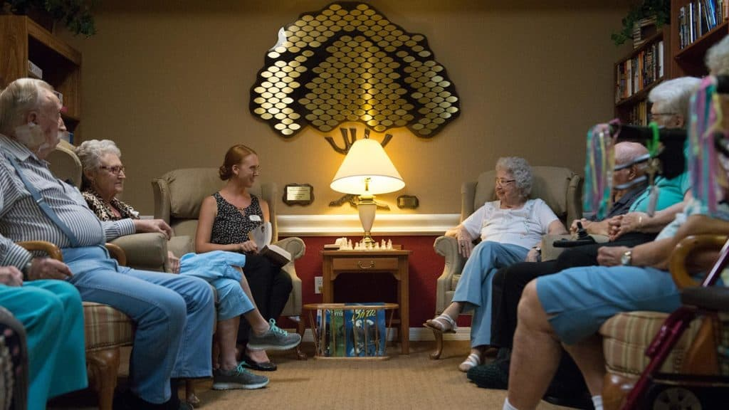 Staff reading to a senior group