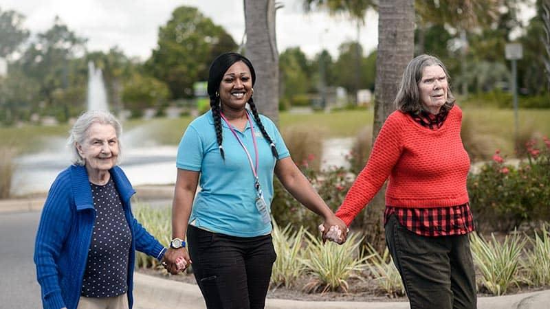 Staff member walking with two senior women